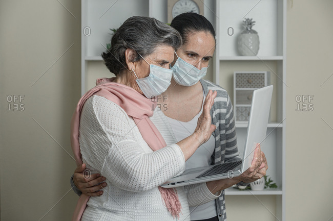 Grandmother and granddaughter in medical mask using laptop to call to relatives while staying at home during coronavirus epidemic