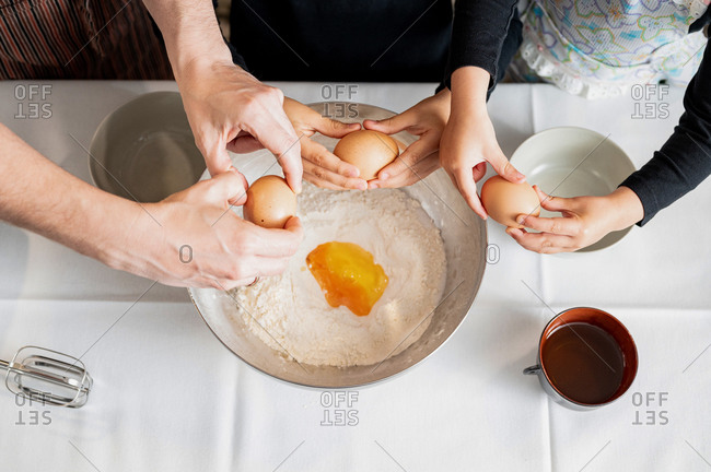 From above anonymous parent and little siblings cracking and adding raw eggs to flour in metal bowl while preparing pastry dough in kitchen together