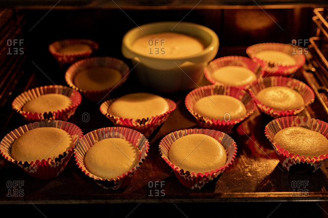Hot oven with homemade baked cupcakes inside at home
