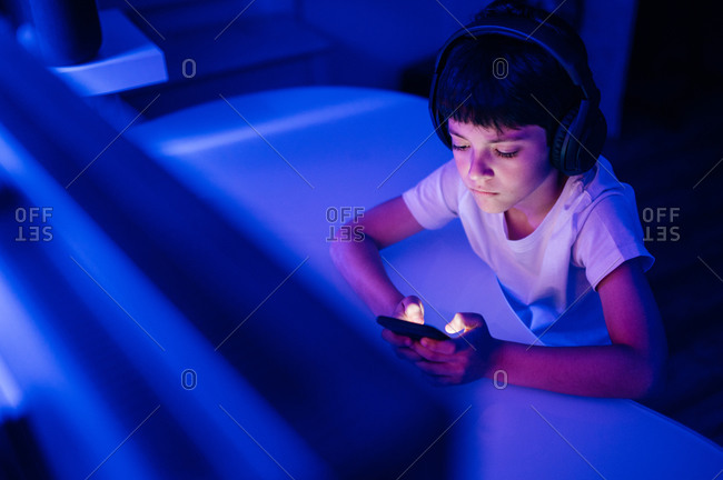Side view of serious boy in headphones surfing internet on cellphone while sitting in front of desktop computer in room with blue light
