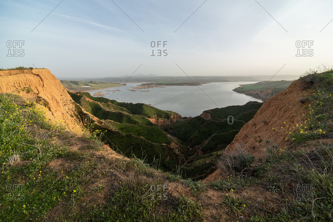 Majestic view of grassy canyon and calm lake located against morning sky in countryside in Barrancas Burujon, Toledo, Spain