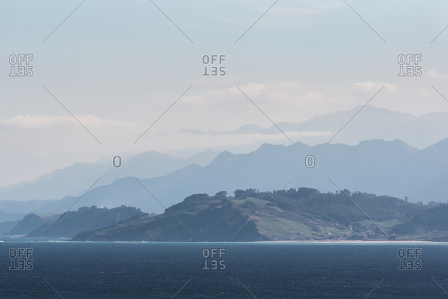 Picturesque seashore surrounded by hills and rocky mountains covered with fog and clouds