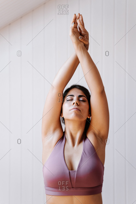 young female in sports bra stretching body with raised arms while performing yoga exercise during training in light room