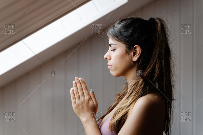 Tranquil fit female in sportswear with clasped hands practicing yoga meditation in modern light room in morning