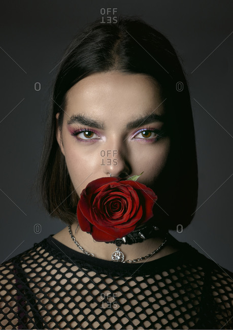 Alluring rebellious young lady with red rose looking at camera