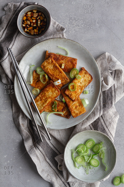 Top view of delicious vegetarian meal fried tofu marinating in soy sauce with garlic and serving in white plate sprinkling with pieces of green onion standing on kitchen towel on gray table with steel Chinese chopsticks