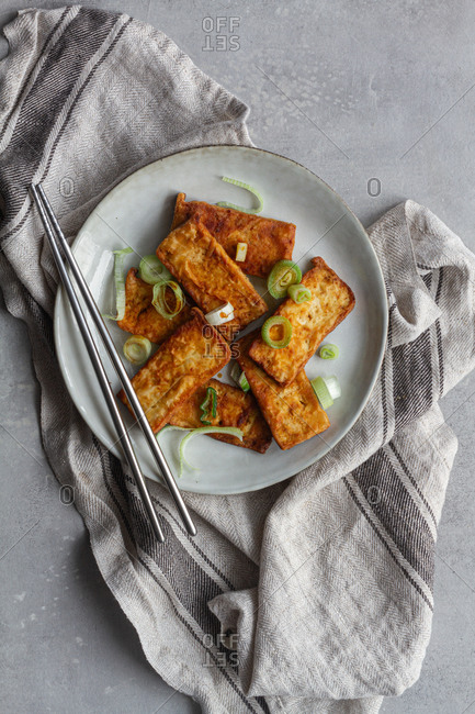Top view of tofu slices with fragrant pieces of garlic marinating in soy sauce in white deep plate while standing on kitchen towel on gray table with steel chopsticks