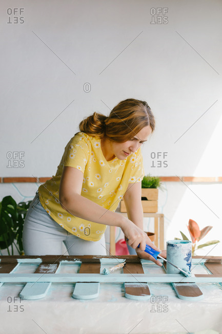 Young blonde woman painting an old fence for her terrace
