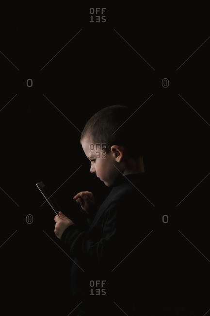 Adorable serious child in casual wear holding tablet in hands with determined look isolated on black background