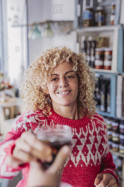 Happy curly hair blonde woman seller bartender with glass cup with wine while working in local delicateness food store