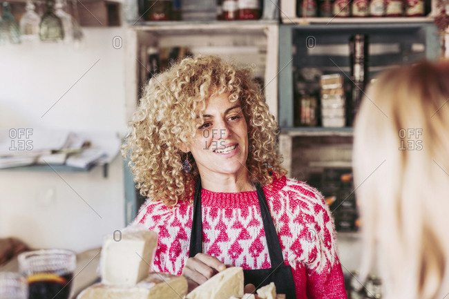 Happy adult woman with curly hair talking with customer while selling cheese in local food delicatessen store