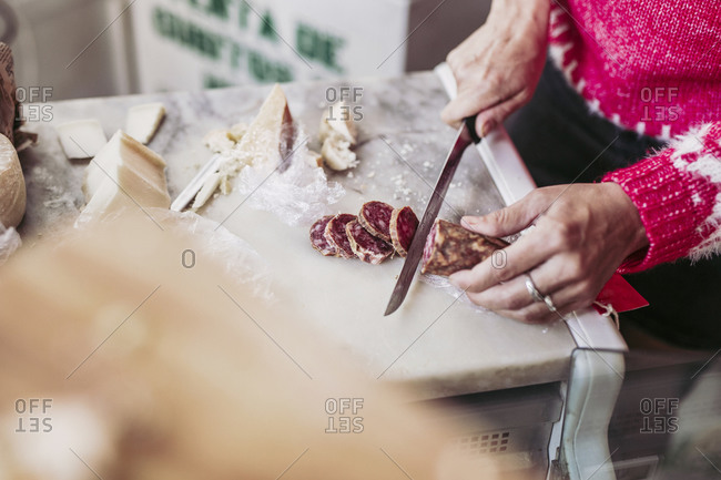 From above anonymous person cutting delicious sausage on counter near cheese while working in local food store