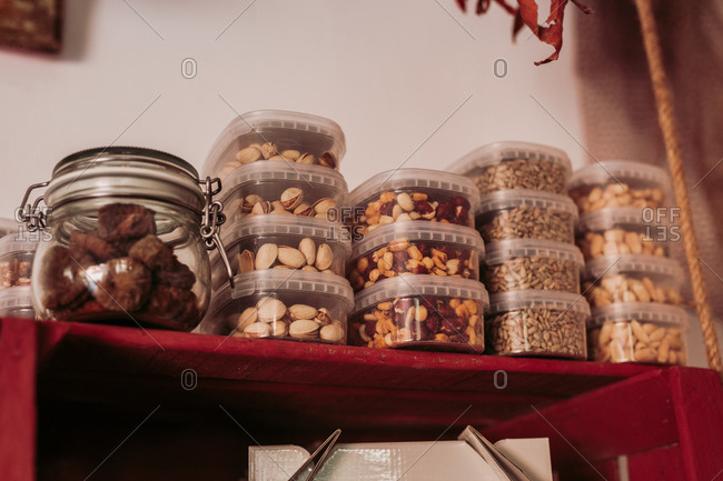 From below glass jar with truffles and plastic boxes with pistachios placed on red wooden shelf in local delicatessen food store