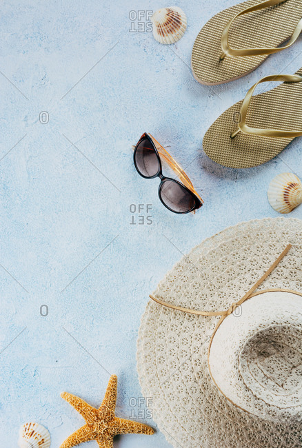 Top view of various seashells placed near stylish summer accessories on blue plaster surface
