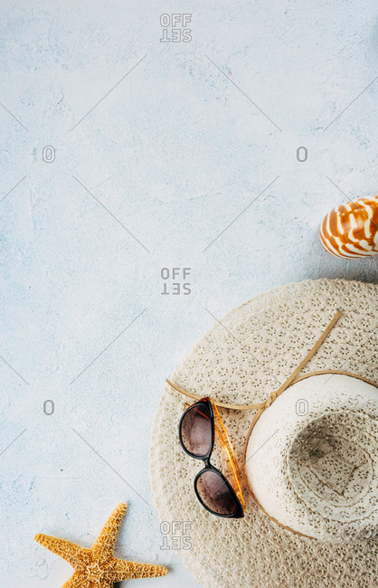Trendy and sunglasses near seashells and starfish for summer vacation concept on plaster surface