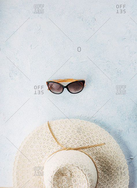 Trendy sunglasses and hat for summer vacation placed near each other on plaster surface
