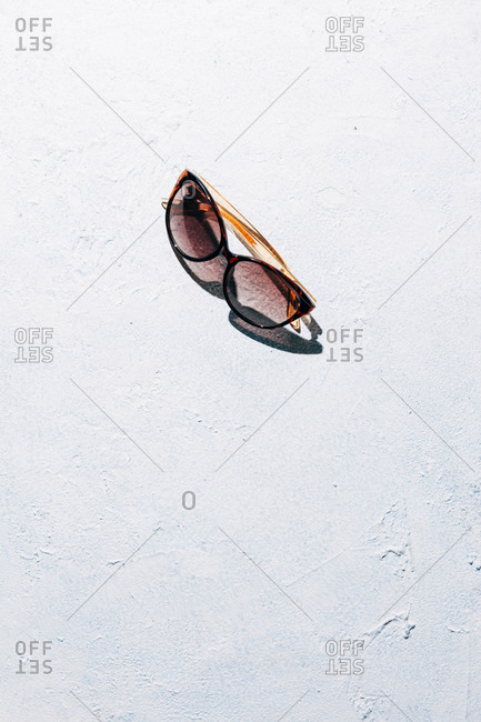 From above trendy sunglasses placed on rough stucco surface on sunny day during summer vacation
