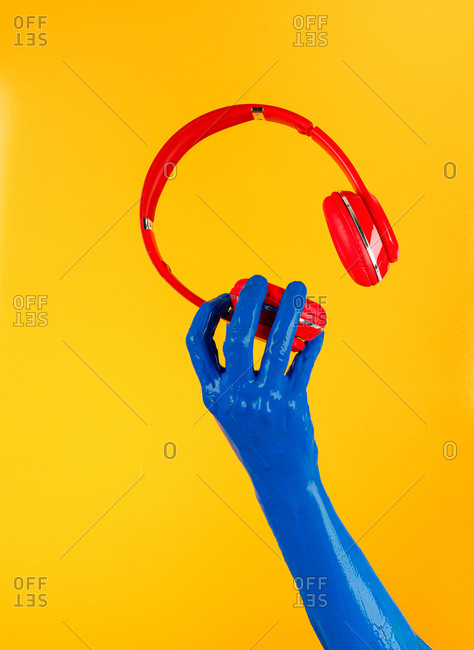 Crop creative person with blue painted hand holding modern headphones on yellow background in studio