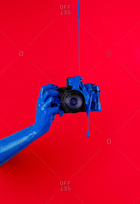 Anonymous person with hand painted in blue color holding modern photo camera poured with gouache and taking picture on red background in studio