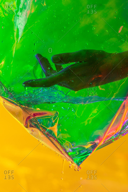 Hand of crop female placed in water in creative transparent plastic handbag on yellow background