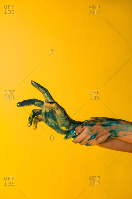 Unrecognizable crop female artist with hands painted in metallic yellow and blue paint