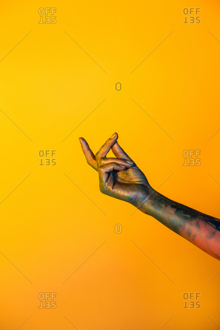 Crop hand of faceless female with painted arm showing snapping gesture on yellow background