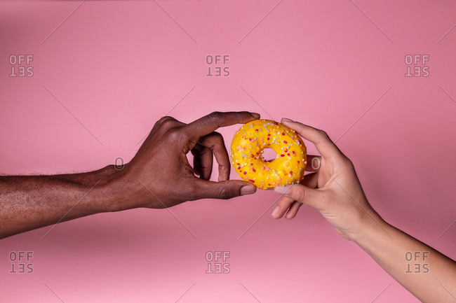 Crop anonymous multiethnic couple holding delicious fresh doughnut on pink background