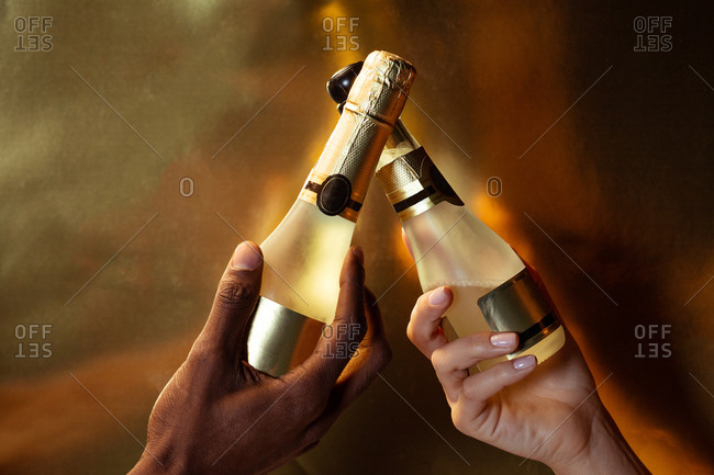 Crop anonymous multiracial couple holding bottles of sparkling wine standing in studio on golden background