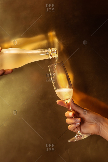 Anonymous crop person holding wineglass while another faceless person pouring champagne into glass from bottle during party on golden background