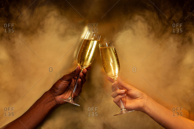 Crop anonymous multiethnic people holding wineglasses with champagne during celebration party on golden background