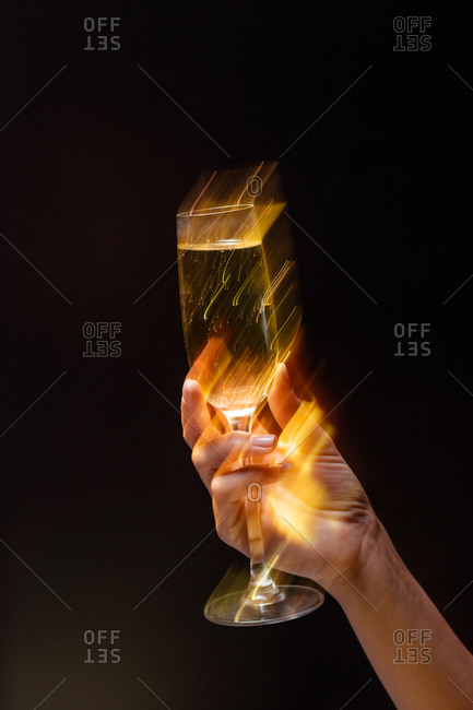 Anonymous crop person holding wineglass with alcohol beverage during holiday party on black background