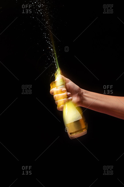 Anonymous crop hand of person holding bottle of cold refreshing beverage on black background