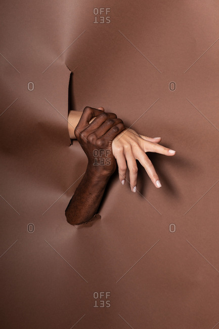 Unrecognizable crop multiethnic couple holding hands while standing behind paper curtain