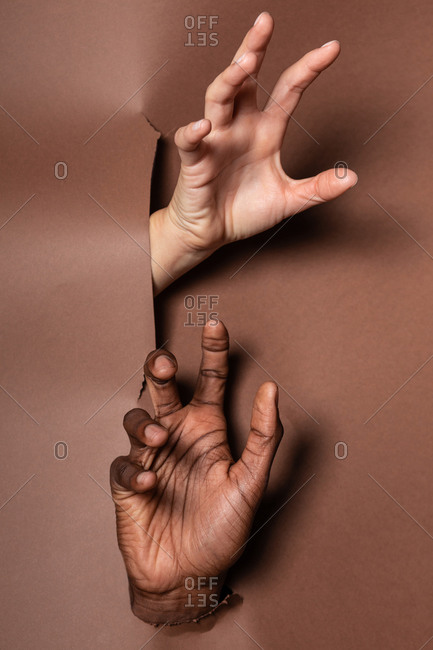 Anonymous crop hands of multiethnic couple demonstrating fingers through hole in paper curtain