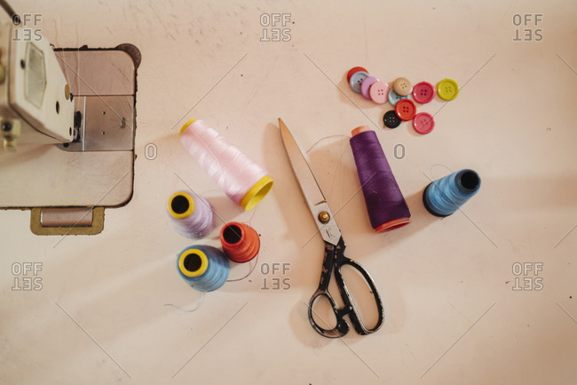 Top view composition of multi colored spools of thread sewing machine buttons and shabby old sewing scissors locating on table in atelier