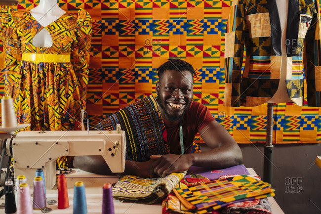 Happy black male tailor creating national costume of colored fabric with African patterns on sewing machine while sitting on background of colored African material and mannequin in sewing workshop