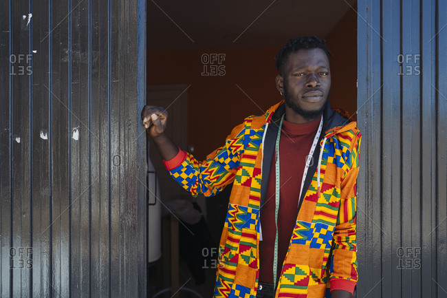 Young serious African American male in orange jacket with multi colored ornament and measuring tape hanging around neck standing near entrance to atelier and looking at camera