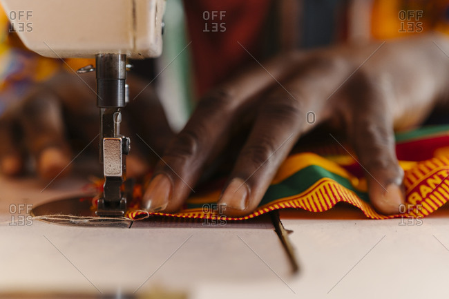 Crop male tailor creating national costume of colored fabric with African patterns on sewing machine while sitting on background of colored African material and mannequin in sewing workshop