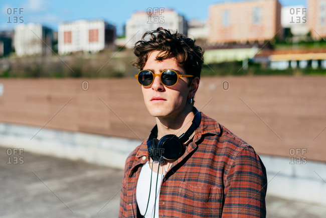Handsome young man in checkered shirt and sunglasses looking at camera while standing on blurred background of city street