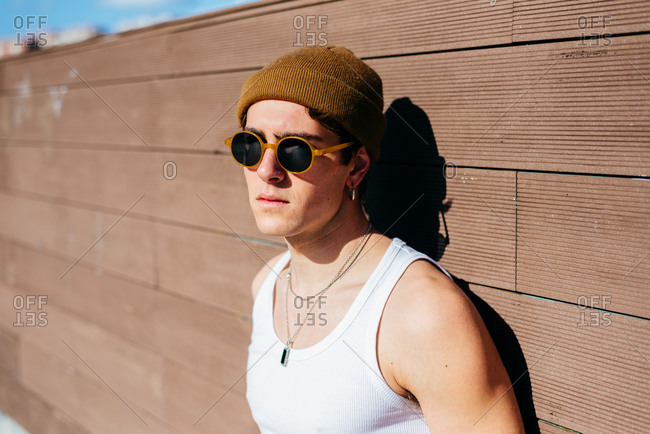 Modern young handsome man in trendy sunglasses and beanie hat and white tank top standing near brown wall on sunny day on city street