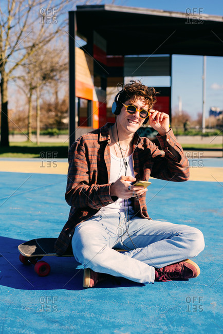 Happy hipster in casual clothes smiling for camera and browsing smartphone while sitting on skateboard and listening to music on sports ground
