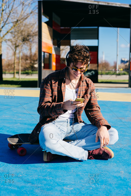 Happy hipster in casual clothes smiling and browsing smartphone while sitting on skateboard and listening to music on sports ground
