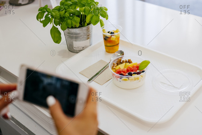 From above of unrecognizable woman taking photo with smartphone while sitting at table in restaurant and eating yummy healthy fruit deserts on white plate
