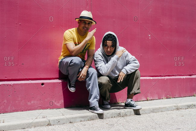 Two young urban dancers standing near to a pink wall on the street