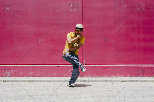 Young Hispanic men dancing near to a pink wall on the street