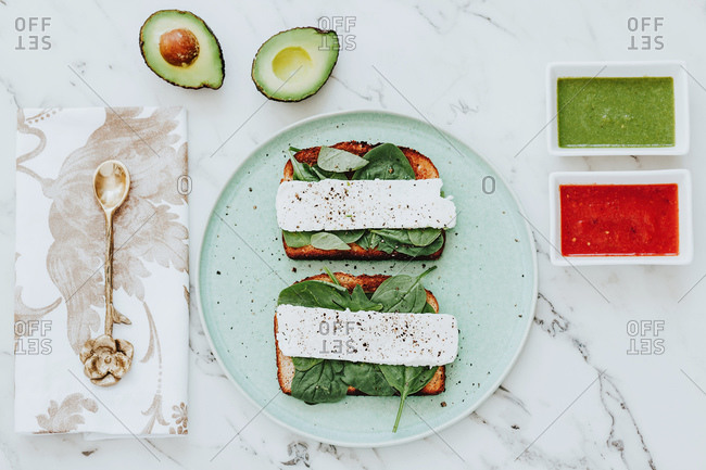 From above plate with cheese and spinach sandwiches place on marble tabletop near napkin with spoon and bowls with avocado and tomato sauces