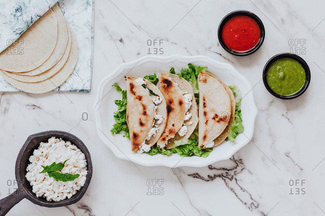 Top view of tortillas with fresh quark cheese placed on plate with lettuce leaves near bowls of avocado and tomato sauces on marble table