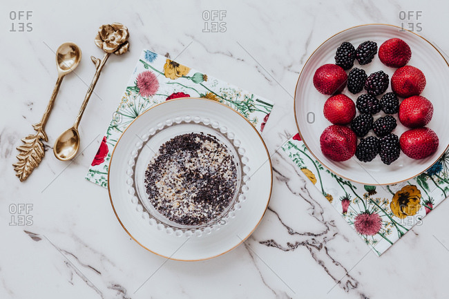 Bowl with delicious poppy seed pudding and plate with strawberries and blackberries placed near paper napkins and ornamental spoons on marble table