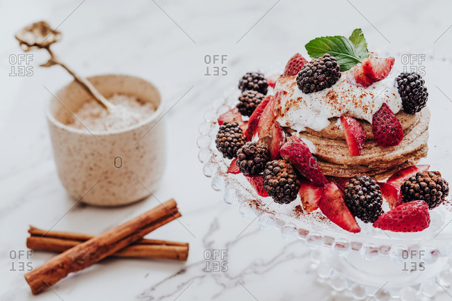 Tasty pancakes with fresh strawberries and blackberries decorated with mint leaf placed on plate near cinnamon sticks and cup of ice cream on marble table