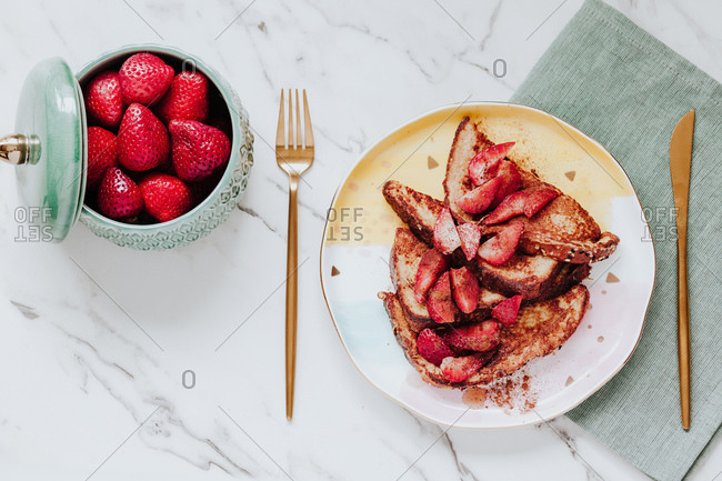 Top view of delicious egg fried bread with ripe strawberries served on plate near cutlery and napkin on marble tabletop